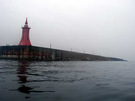 釣り人がいる直江津港の防波堤の先端を回り込む